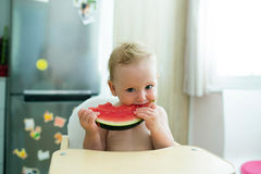 Cute little girl sitting in high chair eating watermelon Stock Images