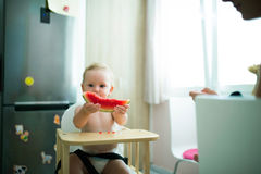 Cute little girl sitting in high chair eating watermelon Stock Image