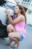 Cute little girl sitting in high heels near car bumper Stock Image