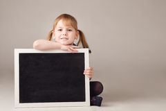 Cute little girl sitting and holding chalkboard isolated on whit Stock Images