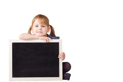 Cute little girl sitting and holding chalkboard isolated on whit Stock Photos