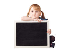 Cute little girl sitting and holding chalkboard isolated on whit Royalty Free Stock Photo