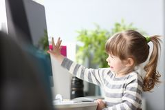Cute little girl sitting at home at worktable working with computer royalty free stock image