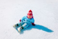 Cute little girl sitting on ice with skates, learning skating. In winter royalty free stock images