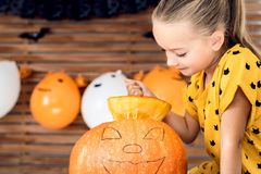 Cute little girl sitting on kitchen table carving large pumpkin. Halloween background. Cute little girl sitting on kitchen table carving large pumpkin stock images