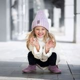 Cute little girl sitting and laughs in knitted hat. Cute little girl sitting and laughs in knitted lilac hat stock photography