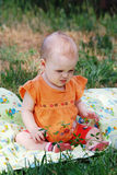 Cute little girl sitting on a meadow Royalty Free Stock Image