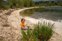 Cute little girl sitting near Bohinj lake during spring time in Slovenia Royalty Free Stock Photography
