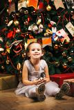 Cute little girl sitting near Christmas tree with gifts and waiting for Christmas Royalty Free Stock Photo
