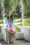 Cute little girl sitting near fountain. Walking. Royalty Free Stock Photos