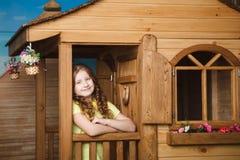 Cute little girl sitting near wood house. Little girl sitting near wood house Stock Photo