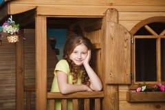 Cute little girl sitting near wood house Stock Photography