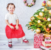 Cute little girl sitting nesxt to the Christmas tree Stock Photos