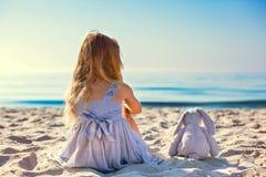 Cute little girl sitting at ocean beach Stock Photo