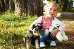 Cute little girl sitting in the park with his dog Stock Photos