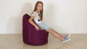 Cute little girl sitting on purple bean bag sofa on white background.Slow motion. Cute little girl sitting on purple bean bag sofa for living room or other room stock video