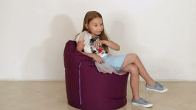 Cute little girl sitting on purple bean bag sofa for living room. Slow motion. Cute little girl sitting on purple bean bag sofa for living room or other room stock video footage
