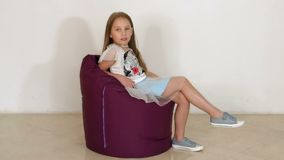 Cute little girl sitting on purple bean bag sofa for living room. Slow motion. Cute little girl sitting on purple bean bag sofa for living room or other room stock footage