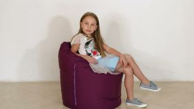 Cute little girl sitting on purple bean bag sofa on white background.Slow motion. A cute little girl in a fluffy skirt sits on purple bean bag sofa on a white stock footage