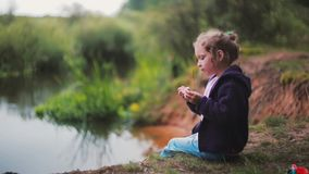 A cute little girl is sitting on a river bank, eating watermelon. Blurred nature at the background. Side view stock footage