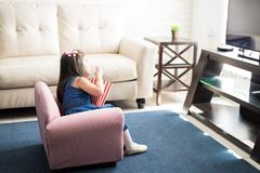Cute girl watching a movie on tv at home Stock Images