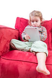 Cute little girl sitting on a sofa with a tablet Royalty Free Stock Photos