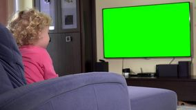 Cute little girl sitting on sofa and watching tv at home. Green chroma key. Screen. Static closeup shot. 4K UHD stock video