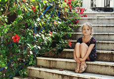 Cute little girl is sitting on the stairs Stock Image