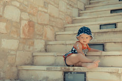 Cute little girl sitting on stairs in the street Stock Photos