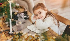 Cute little girl sitting at a table decorated with Chrstmas candels, bokeh lights. Magic christmas atmosphere royalty free stock photo