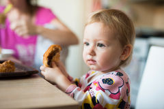 Cute little girl sitting at the table eating croissant Royalty Free Stock Image