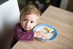 Cute little girl sitting at the table eating mashed potatoes Royalty Free Stock Images