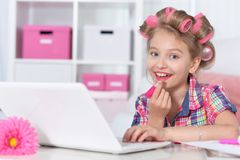 Cute little girl beautifying herselves. Cute little girl sitting at table with laptop and beautifying  herselves Stock Photos