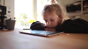 Cute little girl sitting at the table near the window and watching cartoon on tablet computer, putting head on hands. Beautiful, cute little girl sitting near stock video footage