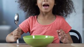 Cute little girl sitting at table with spoon and asking for dinner, hungry kid. Stock photo stock photography