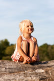 Cute little girl sitting on tree Stock Photo