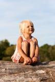 Cute little girl sitting on tree Stock Photo