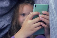Cute little girl sitting under blanket with phone. Cute little girl sitting under blanket with phone royalty free stock images