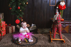 Cute little girl sitting under the Christmas tree. Child playing with a toy train Stock Image