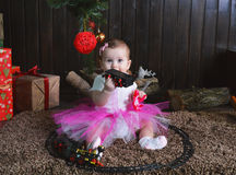 Cute little girl sitting under the Christmas tree. Child playing with a toy train Stock Images