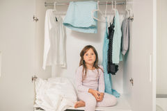 Cute little girl sitting in wardrobe. Cute little girl sitting in mother's wardrobe. Concept happy family with children Royalty Free Stock Image