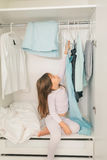 Cute little girl sitting in wardrobe Royalty Free Stock Images