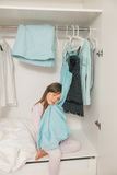 Cute little girl sitting in wardrobe Stock Image