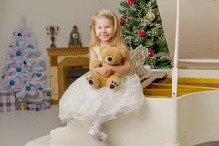 A little girl is sitting on a white piano with a teddy bear. A cute little girl is sitting on a white piano with a teddy bear royalty free stock image