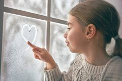 Girl sitting by the window Royalty Free Stock Image