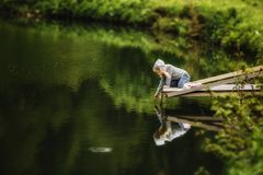 Cute little girl sitting on wooden pier, looking at the mountain lake. Cute little girl sitting on wooden pier, looking at the mountain lake stock photos