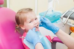 Cute Little girl sitts in dental chair at dentist office, closeup portrait