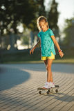 Cute little girl with skateboard outdoors Stock Photo
