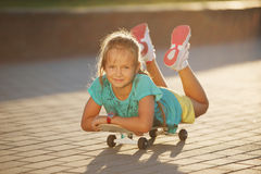 Cute little girl with skateboard outdoors Royalty Free Stock Photography