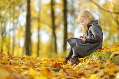 Cute little girl sketching outside on beautiful autumn day. Happy child playing in autumn park. Kid drawing with colourful pencils royalty free stock photo